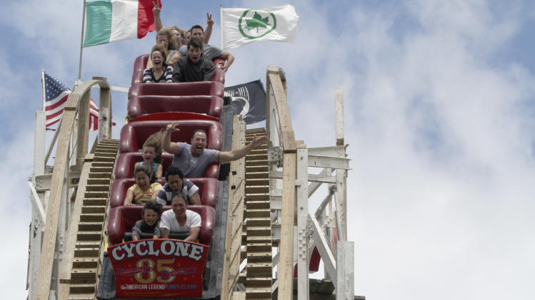 In a Tuesday, June 26, 2012 photo, people ride the Cyclone roller coaster at Coney Island in New York.  The New York City landmark and international amusement icon will be feted Saturday, June 30 with a birthday party in its honor. (AP Photo/Mary Altaffer)