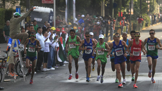 A man sprays water to athletes during the men's marathon 42km at the Pan American Games in Guadalajara, Mexico, Sunday, Oct. 30, 2011.(AP Photo/Ariana Cubillos)