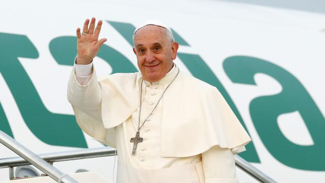 Pope Francis waves as he boards his plane at Fiumicino airport in Rome