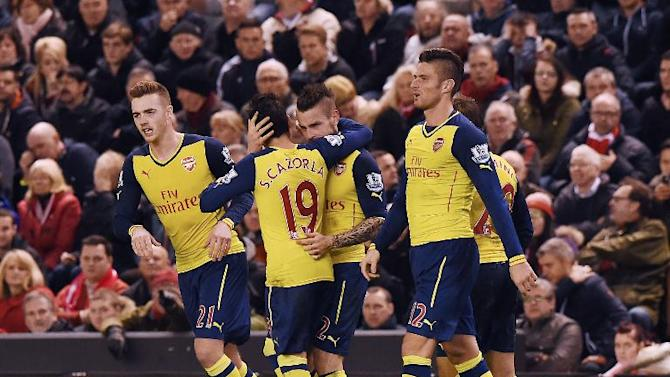 Arsenal's Mathieu Debuchy (C) celebrates scoring the equalising goal with teammates during the English Premier League match against Liverpool at Anfield, on December 21, 2014