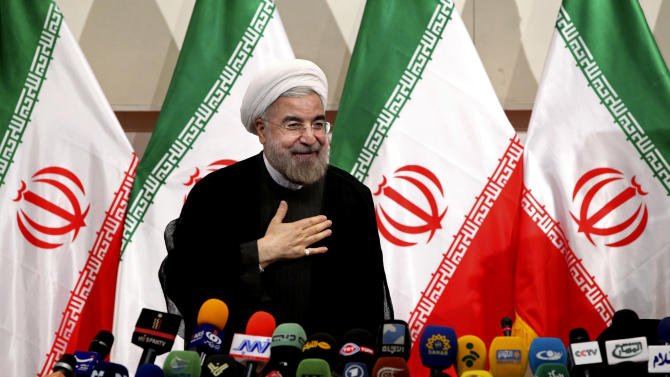 FILE - In this Monday, June 17, 2013 file photo, Iranian President-elect Hasan Rowhani, places his hand on his heart as a sign of respect, after speaking at a news conference, in Tehran, Iran. American officials are hailing Rowhani's victory as the first tangible evidence that the U.S. strategy is affecting Tehran's nuclear policy after wreaking havoc on its economy. The draconian sanctions weighed heavily in the June 14 vote for Rowhani, a candidate who openly criticized how his country's leadership has handled the nuclear file. (AP Photo/Ebrahim Noroozi, File)