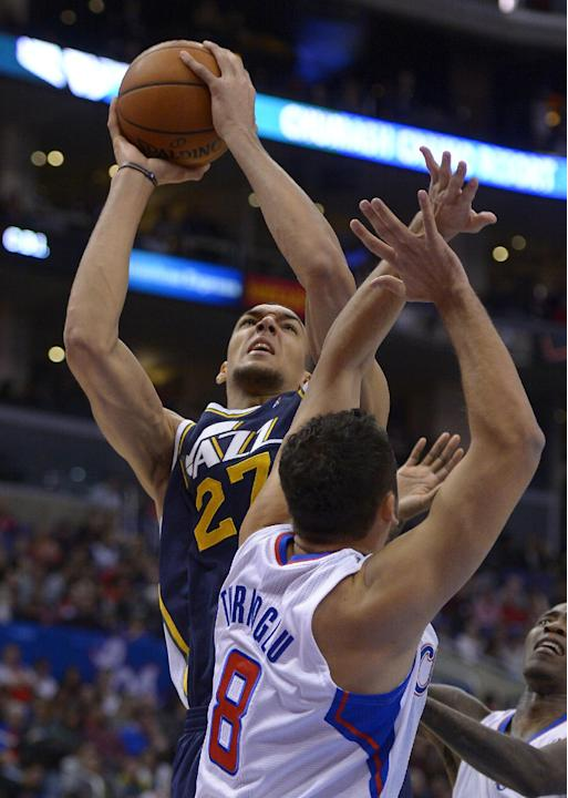 Utah Jazz center Rudy Gobert, left, of France, shoots as Los Angeles Clippers forward Hedo Turkoglu, of Turkey, defends during the first half of an NBA basketball game on Saturday, Feb. 1, 2014, in Lo