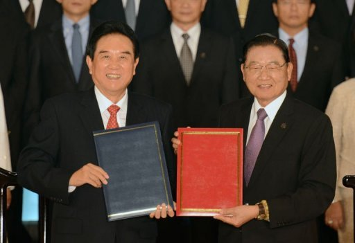 China's chief negotiator Chen Yunlin (L) displays documents with his Taiwanese counterpart Chiang Pin-kung (R)