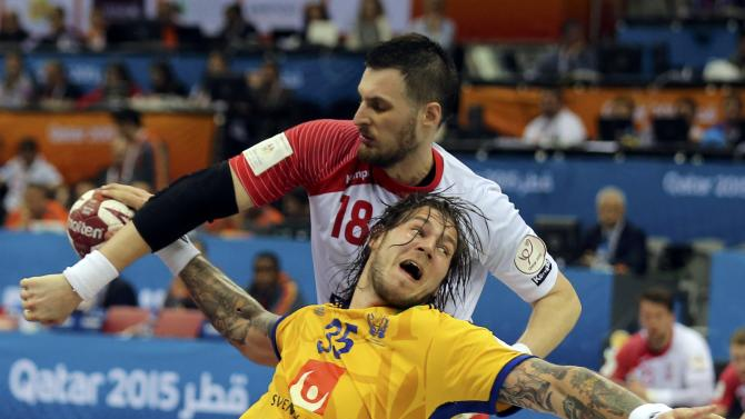 Nilsson of Sweden is blocked by Grabarczyk of Poland during their round of 16 match of the 24th men's handball World Championship in Doha