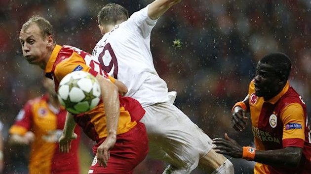 Galatasaray's Semih Kaya (L) and Emmanuel Eboue (R) fight for the ball with CFR Cluj's Pantelis Kapetanos during their Champions League Group H soccer match at Turk Telekom Arena i