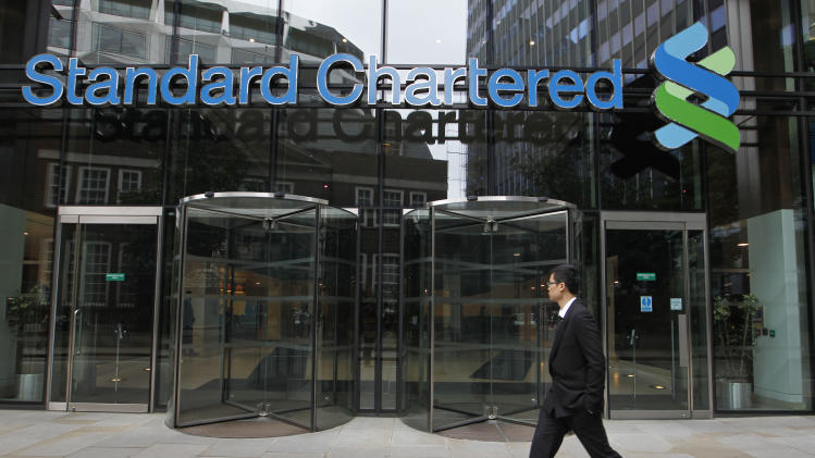"""A man walks by the headquarter of Standard Chartered bank in the City of London, Tuesday, Aug. 7, 2012. Shares in Standard Chartered PLC dropped sharply on Tuesday as investors reacted to U.S. charges that the bank was involved in laundering money for Iran. The charges against Standard Chartered were a shock for a bank which proudly described itself recently as """"boring.""""  (AP Photo/Sang Tan)"""