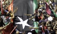 CORRECTS SPELLING OF MOAMMAR - Libyans holding a huge flag celebrate overrunning Moammar Gadhafi's main compound Bab al-Aziziya in Tripoli, Libya, early Wednesday, Aug. 24, 2011. Hundreds of Libyan rebels stormed Gadhafi's compound Tuesday, charging wildly through the symbolic heart of the crumbling regime as they killed loyalist troops, looted armories and knocked the head off a statue of the besieged dictator. (AP Photo/Sergey Ponomarev)