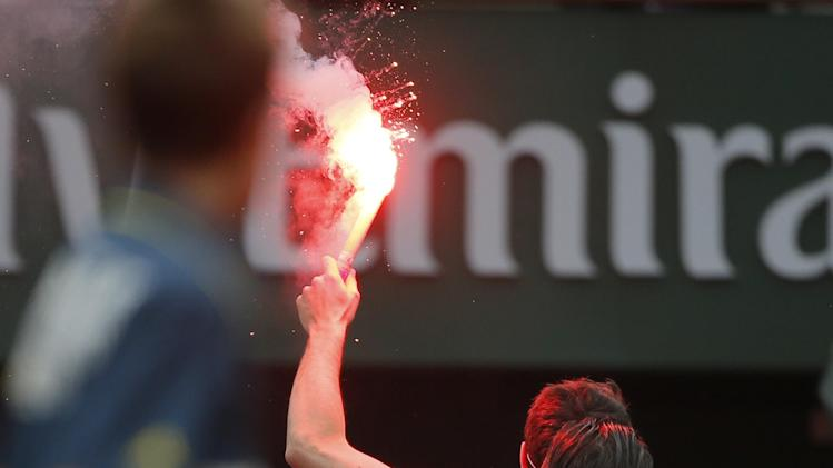 A ball boy watches a security guard remove a demonstrator who ran onto center court as Spain's Rafael Nadal played against compatriot David Ferrer in the final of the French Open tennis tournament, at Roland Garros stadium in Paris, Sunday June 9, 2013. (AP Photo/Michel Spingler)