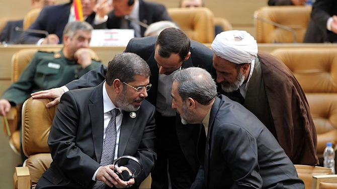 "In this photo released by the official website of the Iranian presidency office, Egyptian President Mohammed Morsi, left, talks with Iranian officials during opening session of Nonaligned Movement, NAM, summit, in Tehran, Iran, Thursday, Aug. 30, 2012. Morsi described the Syrian regime as ""oppressive"" and called for it to transfer power to a democratic system during a visit to Syria's key regional ally Iran on Thursday. Ali Akbar Velayati, advisor to the Iranian supreme leader sits at right. AP Photo/Presidency Office)"