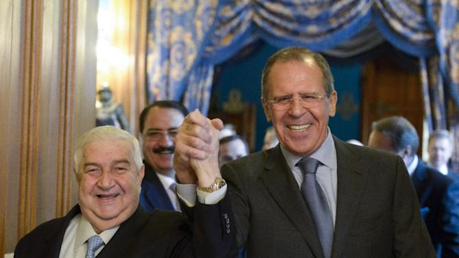 Russian Foreign Minister Sergey Lavrov, right, and Syrian Foreign Minister Walid al-Moallem enter a hall hand in hand for their talks in Moscow, Russia, Friday, Jan. 17, 2014. The Syrian authorities are ready to pool efforts with the opposition to fight terrorists, Muallem said in Moscow on Friday. (AP Photo/Pool)