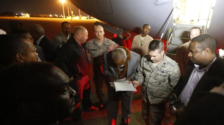 Sudanese official signs release papers of Mohammed Noor and Ibrahim Osman, Sudanese detainees released from the Guantanomo facility in Cuba, before they disembark from a U.S. Air Force plane at Khartoum Airport