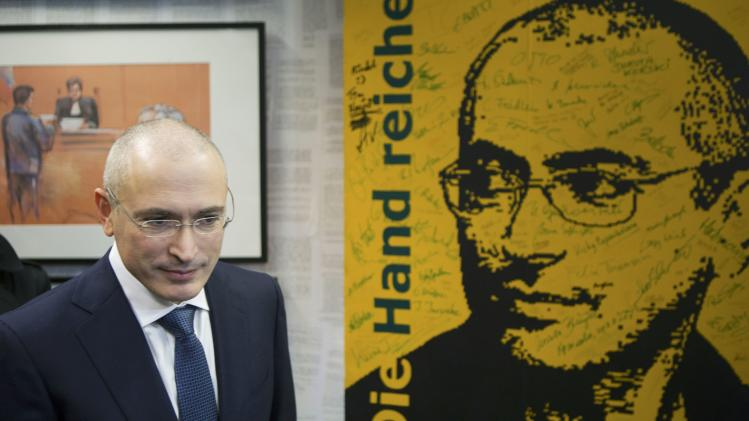 Freed Russian former oil tycoon Khodorkovsky walks past a poster with his picture as he visits an exhibition in the Museum Haus am Checkpoint Charlie in Berlin