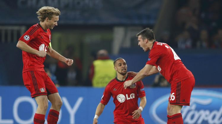 Bayer Leverkusen's Simon Rolfes, Sidney Sam and Giulio Donati celebrate after scoring against Paris St Germain during their Champions League round of 16 second leg soccer match at the Parc des Princes Stadium in Paris