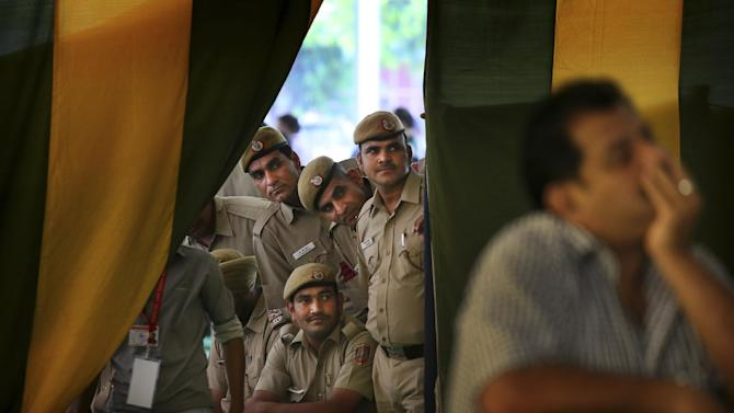 Indian policemen on duty watch election results on television at a counting station in New Delhi, India, Friday, May 16, 2014. India's main Hindu nationalist party was making early gains Friday as officials began counting votes following the country's massive national election, with the opposition looking to end the ruling Congress party's decade-long reign. The Election Commission was expected to announce the results later in the day. (AP Photo/Manish Swarup)