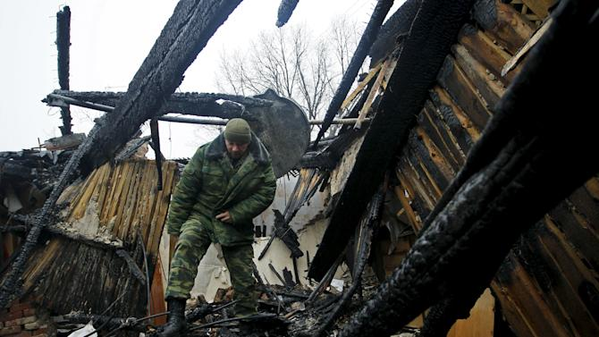 Russian member of the Joint Center on Control and Coordination of issues related to the ceasefire regime walks amidst debris of a house damaged by shelling in Donetsk