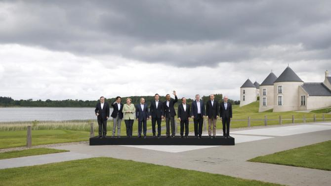 G-8 leaders from left, European Commission President Jose Manuel Barroso, Japan's Prime Minister Shinzo Abe, German Chancellor Angela Merkel, Russian President Vladimir Putin, British Prime Minister David Cameron, US President Barack Obama, French President Francois Hollande, Canadian Prime Minister Stephen Harper, Italian Prime Minister Enrico Letta and European Council President Herman Van Rompuy pose during a group photo opportunity during the G-8 summit at the Lough Erne golf resort in Enniskillen, Northern Ireland, on Tuesday, June 18, 2013. The final day of the G-8 summit of wealthy nations is ending with discussions on globe-trotting corporate tax dodgers, a lunch with leaders from Africa, and suspense over whether Russia and Western leaders can avoid diplomatic fireworks over their deadlock on Syria's civil war. (AP Photo/Matt Dunham)