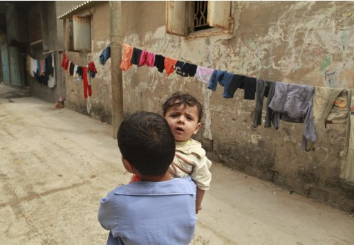 A Palestinian boy carries his brother in Shati refugee camp in Gaza City