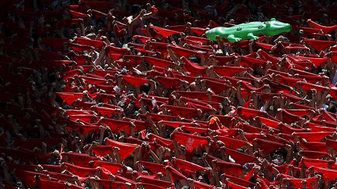 Revellers hold up red scarves during the start of the San Fermin Festival in Pamplona