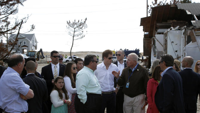 Britain's Prince Harry, center, and N.J. Gov. Chris Christie, center left, listen to Mantoloking Mayor George Nebel, center right, speak while visiting the area hit by Superstorm Sandy, Tuesday, May 14, 2013, in Mantoloking. Prince Harry began a tour  of New Jersey's storm-damaged coastline, inspecting dune construction, walking past destroyed homes and shaking hands with police and other emergency workers.  New Jersey sustained about $37 billion worth of damage from the storm. (AP Photo/Mel Evans, Pool)