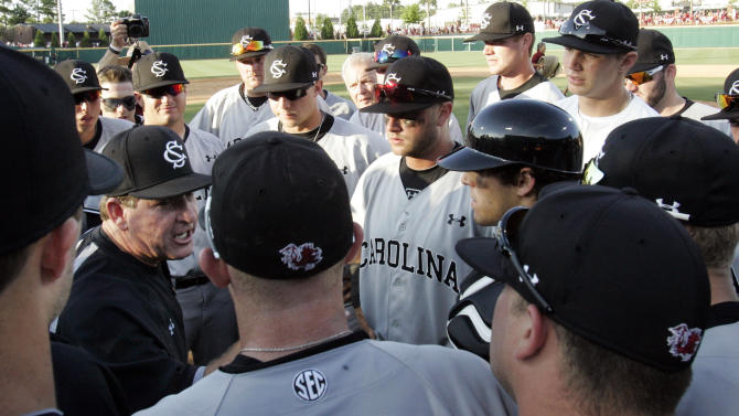 South Carolina coach Ray Tanner, left, talks to his players after defeating Clemson 4-3 in their NCAA college baseball tournament regional in Columbia, S.C., Sunday, June 3, 2012. (AP Photo/Mary Ann Chastain)