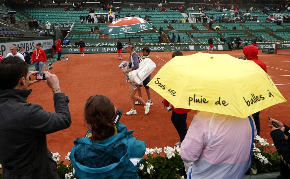 Russia's Maria Sharapova leaves the court after another rain delay as she plays Canada's Eugenie Bouchard during their second round match of the French Open tennis tournament at the Roland Garros stadium Thursday, May 30, 2013 in Paris. On yellow umbrella: It's raining balls. (AP Photo/Petr David Josek)
