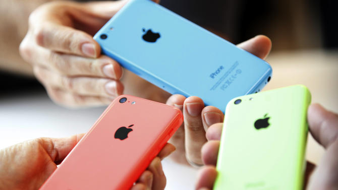People check out several versions of the new iPhone 5C after Apple Inc's media event in Cupertino