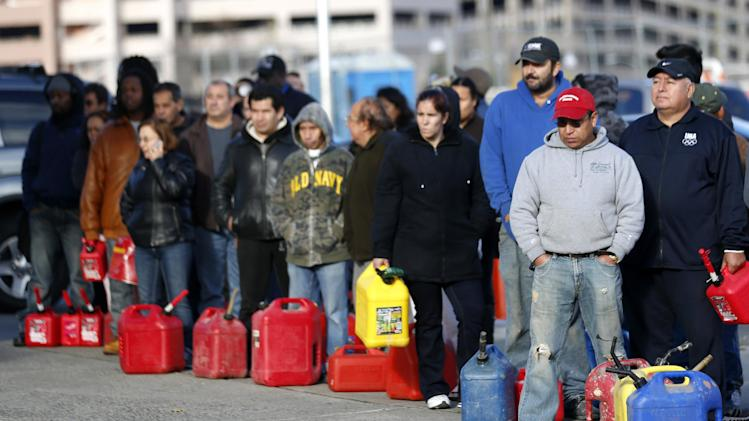 People line up at a gas station waiting to fill up, Friday, Nov. 2, 2012, in Newark, N.J. In parts of New York and New Jersey, drivers lined up early Friday for hours at gas stations that were struggling to stay supplied. The power outages and flooding caused by Superstorm Sandy have forced many gas stations to close and disrupted the flow of fuel from refineries to those stations that are open. (AP Photo/Julio Cortez)