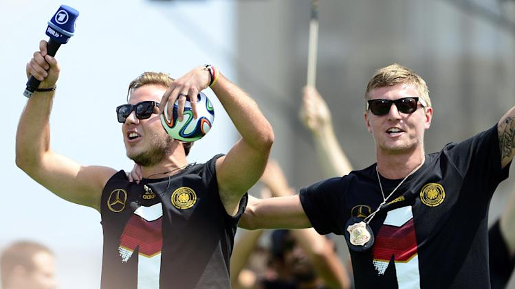 Germany striker Mario Goetze (L) and midfielder Toni Kroos cheer during celebrations for the World Cup-winning German national football team at Berlin's landmark Brandenburg Gate on July 15, 2014