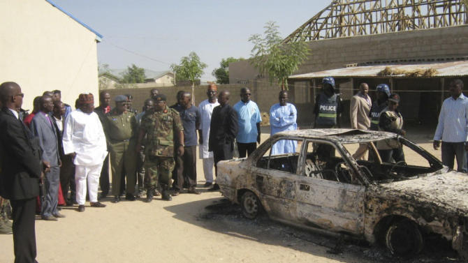Bystanders gather around a burned car outside the Victory Baptist Church in Maiduguri, Nigeria, Saturday, Dec. 25, 2010. Authorities say dozens of assailants attacked the church on Christmas Eve, killing the pastor, two members of the choir and two people passing by the church. Police are blaming members of Boko Haram, a radical Muslim sect. (AP Photo - Njadvara Musa)