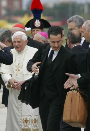 """FILE- In this Monday, April 21, 2008 file photo, Pope Benedict XVI's butler Paolo Gabriele, right, carries the pontiff's bags as they arrive at Ciampino military airport in Rome from a six-day trip in the U.S. Pope Benedict XVI's ex-butler Paolo Gabriele and another Vatican lay employee, Claudio Sciarpelletti, are scheduled to go on trial Saturday, Sept. 29, 2012, in the embarrassing theft of papal documents that exposed alleged corruption at the Holy See's highest levels. Gabriele was arrested May 24 after Vatican police found what prosecutors called an """"enormous'' stash of documents from the pope's desk in his Vatican City apartment. (AP Photo/Domenico Stinellis, File)"""