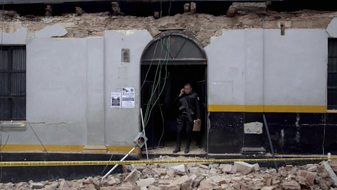 A  police officer stands in the archway of a building damaged by a magnitude 7.4 earthquake that struck in San Marcos, Guatemala, Wednesday, Nov. 7, 2012. The mountain village, some 80 miles (130 kilometers) from the epicenter, suffered much of the damage with some 30 homes collapsing in its center. There are three confirmed dead and many missing after the strongest earthquake to hit Guatemala since a deadly 1976 quake that killed 23,000. (AP Photo/Moises Castillo)