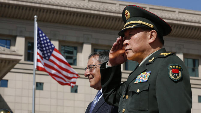 U.S. Defense Secretary Leon Panetta, left, stands at attention next to China's Defense Minister Liang Guanglie at the Bayi Building in Beijing, China Tuesday, Sept. 18, 2012. (AP Photo/Larry Downing, Pool)
