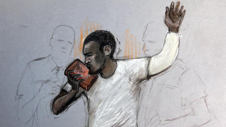 In this court artist sketch by Elizabeth Cook, suspect Michael Adebolajo kisses the Qu'ran, as he appears at Westminster Magistrates Court, London, Monday June 3, 2013. A man accused of killing British soldier Lee Rigby has made his first appearance in court. Michael Adebolajo faces various charges including murder, attempted murder and firearms possession. His suspected accomplice, Michael Adebowale, was expected to make a separate court appearance Monday. Both men were injured and placed under armed guard in hospital after the attack on Rigby, an off-duty soldier who was killed while walking back to his military barracks in southeast London. (AP Photo/ Elizabeth Cook, PA) UNITED KINGDOM OUT