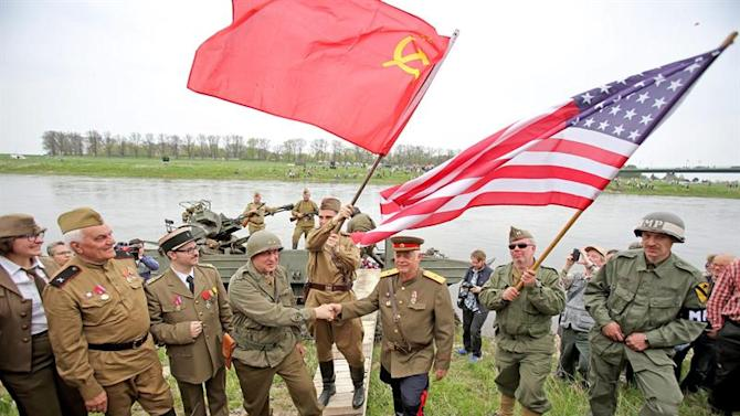 LEI226. Torgau (Germany), 25/04/2015.- Participants reenact the historic handshake meeting between Soviet and US soldiers toward the end of World War II with a Russian amphibious vehicle near Torgau, Germany, 25 April 2015 - this year on its 70th anniversary. During the so-called 'Elbe Day' the city of Torgau celebrates the meeting between Soviet and US army units at the Elbe river which heralded the near end of World War II. (Alemania) EFE/EPA/JAN WOITAS