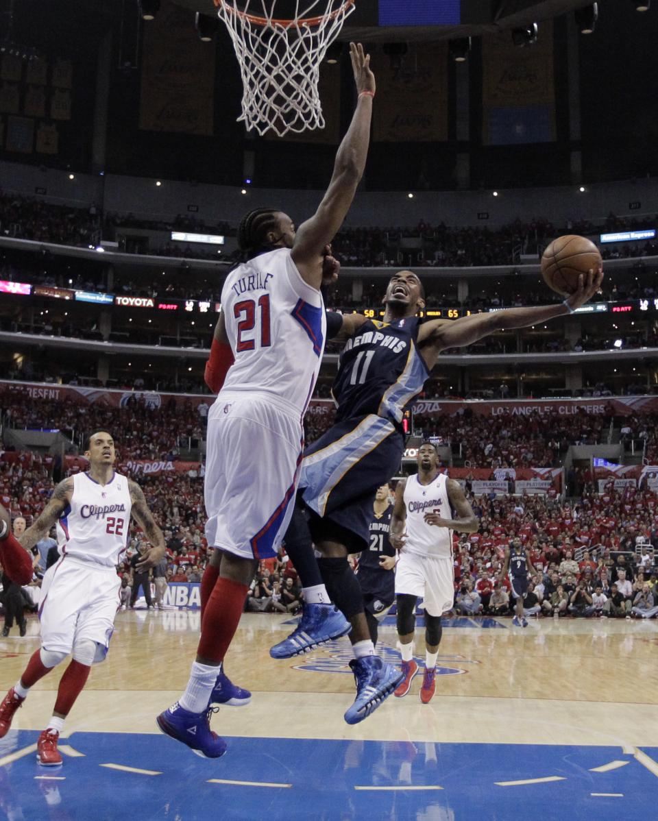 Memphis Grizzlies' Mike Conley, right, puts up a shot against Los Angeles Clippers' Ronny Turiaf during the second half in Game 5 of a first-round NBA basketball playoff series in Los Angeles, Tuesday, April 30, 2013. The Grizzlies won 103-93. (AP Photo/Jae C. Hong)