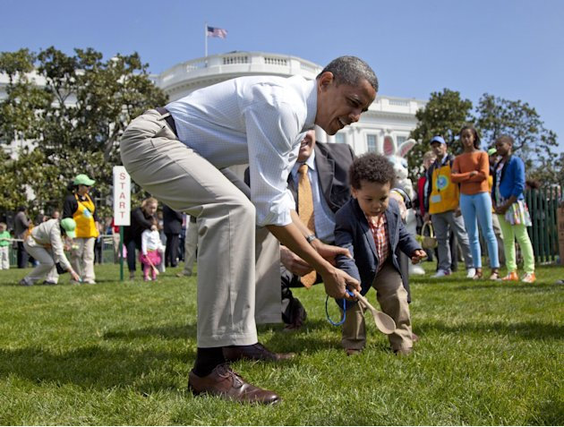 President Barack Obama helps a little boy roll his egg to the finish line during the annual White House Easter Egg Roll, Monday, April 9, 2012, on the South Lawn of the White House in Washington.  In