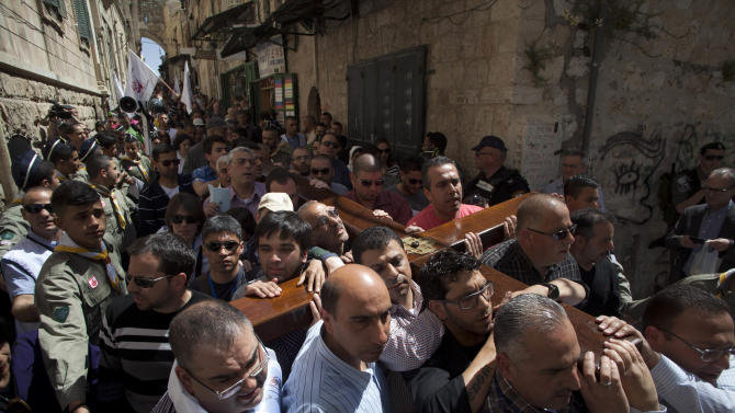 Christian worshippers carry a cross towards the Church of the Holy Sepulcher, traditionally believed by many to be the site of the crucifixion of Jesus Christ, during the Good Friday procession in Jerusalem's Old City, Friday, March 29, 2013. Less than 2 percent of the population of Israel and the Palestinian territories is Christian, mostly split between Catholicism and Orthodox streams of Christianity. Christians in the West Bank wanting to attend services in Jerusalem must obtain permission from Israeli authorities. Israel's Tourism Ministry said it expects some 150,000 visitors in Israel during Easter week and the Jewish festival of Passover, which coincide this year. (AP Photo/Sebastian Scheiner)