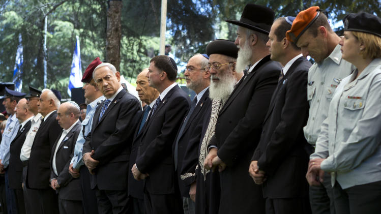 Israeli Prime Minister Benjamin Netanyahu, center left, marks Remembrance Day in the Mount Herzl Military Cemetery in Jerusalem, Israel, Monday, April 15, 2013. The sad atmosphere ends sharply at sundown when in jarring contrast, Israelis joyfully take to the streets for independence day celebrations with dancing, fireworks and parties. (AP Photo/Jim Hollander, Pool)