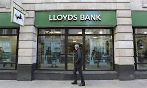 A man walks past a branch of Lloyds bank in central London