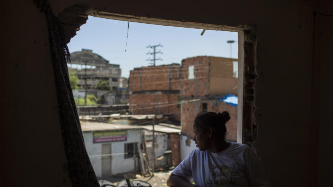 In this Jan. 9, 2014 photo, a resident looks from her window at the Favela do Metro slum near Maracana stadium where some homes have been demolished in Rio de Janeiro, Brazil. Residents in this slum were evicted from their homes two years ago for the area to be renovated for the 2014 World Cup and 2016 Olympics, but people reoccupied the homes and are fighting to stay. (AP Photo/Felipe Dana)