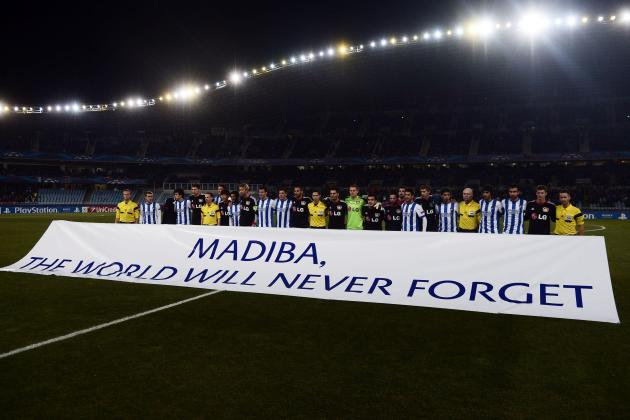Real Sociedad and Bayer Leverkusen players pose in front of a banner in rememberence of Nelson Mandela reading before their Champions League soccer match at Anoeta stadium in San Sebastian