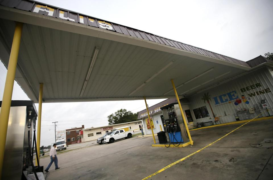Convenience store owner Ali Karimi walks across the gas filling lanes in front of his store, Tuesday, Oct. 29, 2013, in Terrell, Texas. Authorities say five people were shot and killed, including a clerk at the store, by a single gunman in a shooting spree. (AP Photo/Tony Gutierrez)