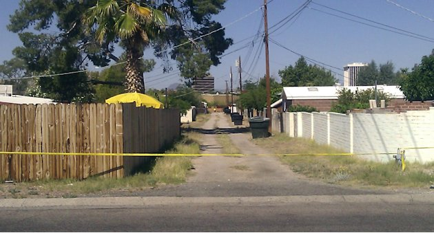 An alley path behind the street where a 6-year-old Tucson girl went missing from her home is cut off with police tape in Tucson, Ariz., Sunday, April 22, 2012. Police cordoned off a neighborhood block