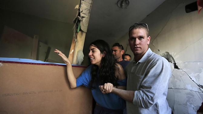 Israelis Sapir, left, and her boyfriend Ron, right, last names not given, walk inside Sapir's home, hit by a rocket fired by militants from Gaza Strip, in the southern city of Beersheba, Israel, Tuesday, Nov. 20, 2012. Efforts to end a week-old convulsion of Israeli-Palestinian violence drew in the world's top diplomats on Tuesday, with President Barack Obama dispatching his secretary of state to the region on an emergency mission and the U.N. chief appealing from Cairo for an immediate cease-fire.(AP Photo/Tsafrir Abayov)