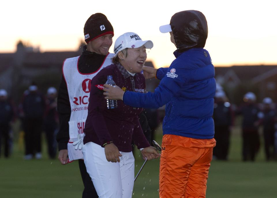 Korea's Jiyai Shin is doused with water by fellow Korean So Yeon Ryu, right, as her caddy Florian Rodriguez looks on after winning the Women's British Open golf championships at Royal Liverpool Golf Club, Hoylake, England, Sunday Sept. 16, 2012.  (AP Photo/Jon Super)