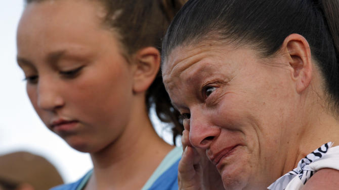 "Renee Pacheco, right, from Albacqure, N.M., wipes a tear from her face, Sunday, July 22, 2012, in Aurora, Colo., during a prayer vigil for the victims of Friday's mass shooting at a movie theater. Twelve people were killed and dozens were injured in a shooting attack early Friday at the packed theater during a showing of the Batman movie, ""The Dark Knight Rises."" Police have identified the suspected shooter as James Holmes, 24. (AP Photo/Alex Brandon)"