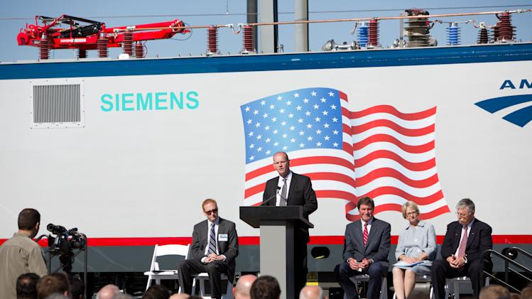 IMAGE DISTRIBUTED FOR SIEMENS USA - Michael Cahill, president of Siemens Rail Systems division in the U.S. speaks at the unveiling of Siemens next-generation locomotives at the Siemens rail facility on Monday, May 13, 2013 in Sacramento, Calif. On stage are from left, Nathan Dietrich, district director for Rep. Doris Matsui, Rep. John Garamendi, Karen Hedlund, Deputy Federal Rail Administrator and Joseph Boardman, president and CEO of Amtrak. (John Decker/AP Images for Siemens USA)