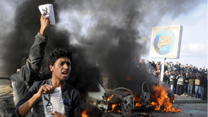 """FILE - In this Friday, Dec. 14, 2012 file photo, opponents of Egyptian President Mohammed Morsi hold pamphlets urging a """"no vote"""" on a constitutional referendum as cars burn during clashes between supporters and opponents of President Mohammed Morsi in Alexandria, Egypt. This Mediterranean city with a cosmopolitan heritage, now an Islamist stronghold, is often seen as a predictor of Egypt's trends. So a ferocious battle between sword-wielding Islamists and rock-throwing opponents outside a revered mosque last weekend could be a sign of the volatile direction the country's crisis is taking: Islamists are threatening to take up arms, and young, secular activists are growing bolder in rebelling against their domination. (AP Photo, File)"""