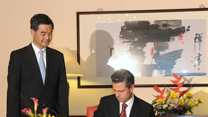 Hong Kong Chief Executive Leung Chun-Ying, left, watches as Mexican President Enrique Pena Nieto, right, signs the guest book before their official talks at Government House in Hong Kong on Friday April 5, 2013.  Enrique Pena Nieto arrived in Hong Kong on a trip aimed at deepening economic ties and widening relations with the Asia-Pacific region. (AP Photo / Dale de la Rey)