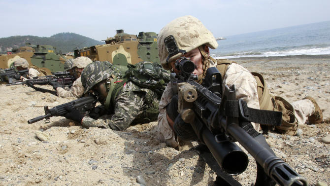 South Korean and U.S. Marines aim their machine guns during the U.S.-South Korea joint landing exercises called Ssangyong, part of the Foal Eagle military exercises, in Pohang, South Korea, Monday, March 31, 2014. South Korea said North Korea has announced plans to conduct live-fire drills near the rivals' disputed western sea boundary. The planned drills Monday come after an increase in threatening rhetoric from Pyongyang and a series of rocket and ballistic missile launches in an apparent protest against the annual military exercises by Seoul and Washington. (AP Photo/Ahn Young-joon)